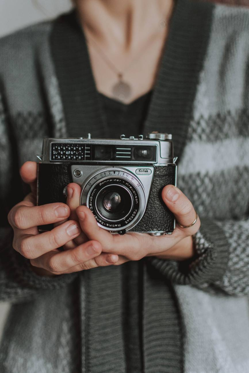 woman holdinng black analogue camera