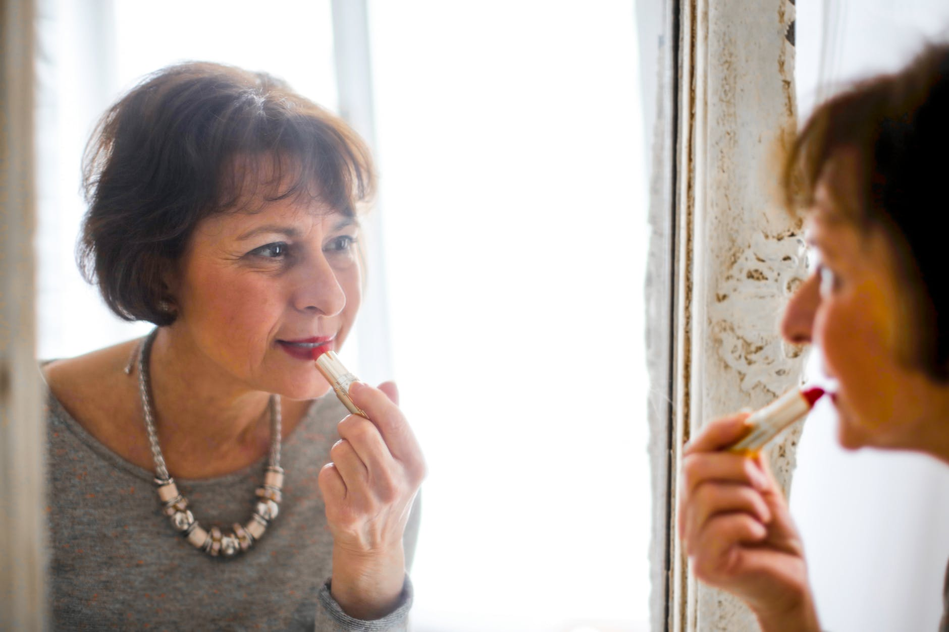photo of older woman applying lipstick in front of the mirror