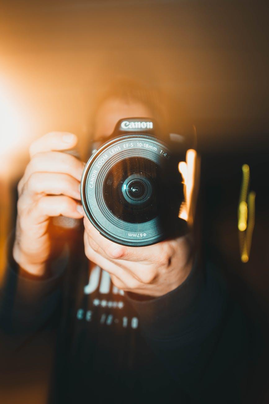 person holding black nikon dslr camera